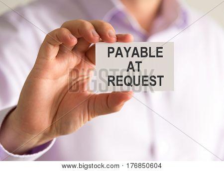 Businessman Holding A Card With Payable At Request Message