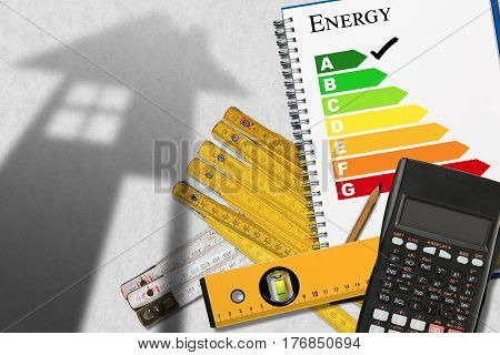 Energy efficiency rating graph in a notebook with a shadows of a house calculator wooden folding rulers spirit level and a pencil