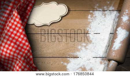 Rolling pin with white flour on a wooden table with an empty label with copy space and a red and white checkered tablecloth