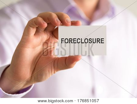 Businessman Holding A Card With Foreclosure Message