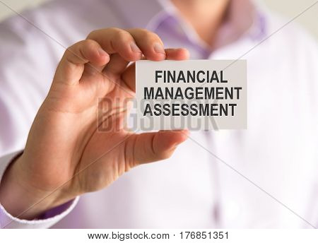 Closeup on businessman holding a card with FINANCIAL MANAGEMENT ASSESSMENT message business concept image with soft focus background poster