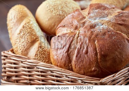 Different white bread in the wicker basket on the brown background. Close-up. Baker and tasty. Natural materials and products. Wooden basket.