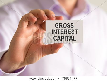 Businessman Holding A Card With Gross Interest Capital Message