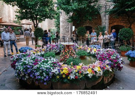 Barcelona Spain - May 29 2016: Feast of Corpus Christi. People look at the egg on dancingin the fountains decorated with colorful flowers at gothic district of Barcelona