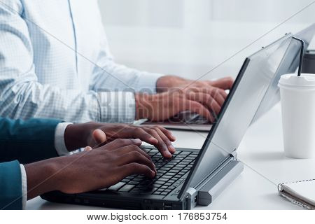 Programming using new technologies. Learning computer programs online. Multiethnic office workers