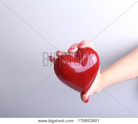 Female doctor hold in hands red toy heart and stethoscope. Cardio therapeutist, arrhythmia concept.