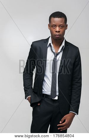 Fashion show, collection of designed clothes. African american guy model in elegant suit on grey background with free space.