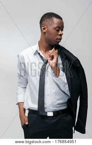 Fashion show, collection of designed clothes. African american guy model in elegant suit on grey background.