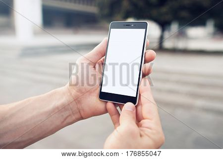 Searching for location with online smartphone maps. Hands holding blank screen smartphone with clipping path for screen