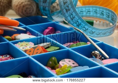 Accessories for needlework in a box with cells. Stuff. Small depth of sharpness. Horizontal format. Indoors. Without people. Color. Photo.