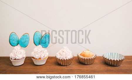 Delicious cupcakes with white cream and blue cakepops in row placed on wooden surface. White background with copyspace for text. Concept of creating sweets. Baking and cake decorating timeline