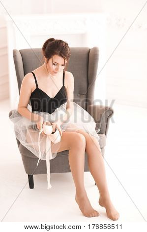 Ballet dancer girl wearing leotard and skirt holding pointe shoes sitting in retro chair. Posing in room. 20s.