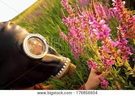 Woman with gas mask looking pink flowers