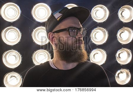 Man With A Beard. Portrait Of A Bearded Guy In A Cap Against A Backdrop Of Light Bulbs
