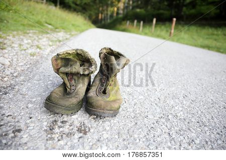 a pair of old worn hiking shoes on a way