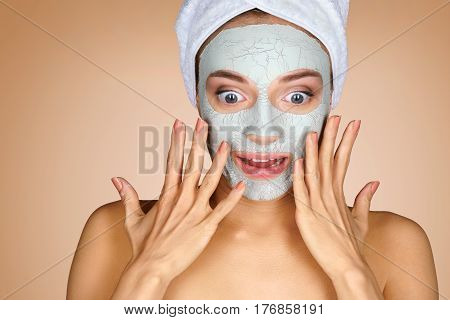 OMG! Surprised girl with opened mouth. Photo of young girl with towel on her head and clay facial mask on beige background. Skin care concept