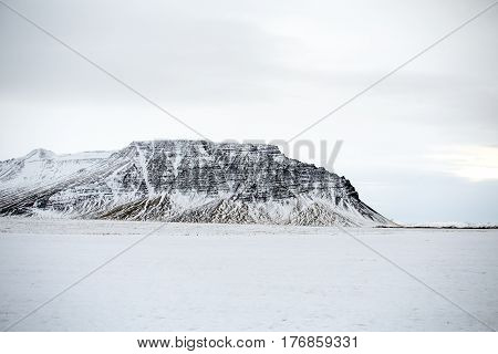 Snow covered mountain range with high contrast black volcanic rock