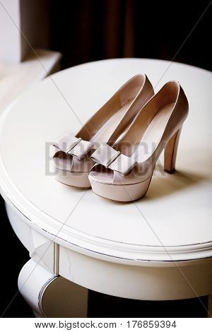 Pair of elegant brides biege shoes on small round table