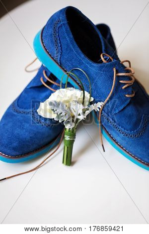 Pair of elegant grooms blue suede brogue shoes with tenderless boutonniere