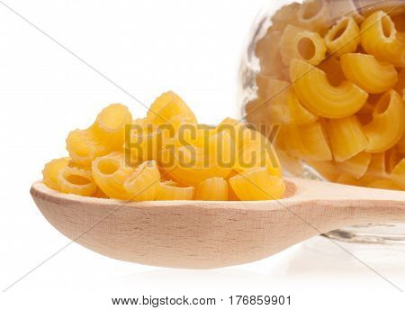 Raw macaroni in the wooden spoon and glass can isolated on white background