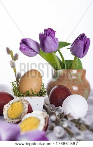 Easter eggs in composition with tulips and willow twigs. Happy Easter.