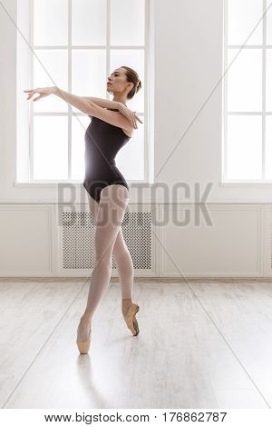 Classical Ballet dancer training. Beautiful graceful ballerine in black practice ballet positions near large window in light hall. Ballet class, high-key soft toning. Vertical image