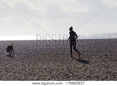 BRIGHTON GREAT BRITAIN - FEB 28 2017: Brighton beach made of pebbles during the morning a woman and dog jogging. February 28 2017 in Brighton Great Britain