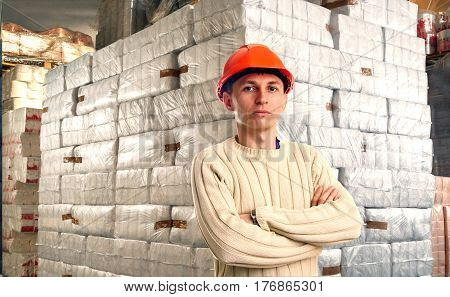 Workman in red helmet inside goods storehouse