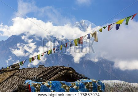 High Mountains View with Nepalese prayer flags garland and roofs of Village buildings on foreground on sunny day with beautiful clouds