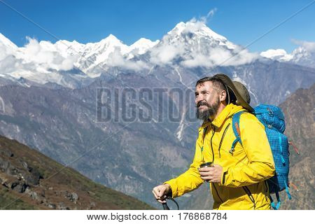 Portrait of bearded mature Hiker in yellow Jacket holding Tea Mug and walking Pole with blue Backpack standing in front of Mountain Landscape and smiling