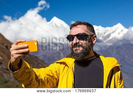 Smiling Bearded Man in bright sporty Jacket taking Photo Self Portrait or Video with mobile Telephone in front of Mountain Panorama