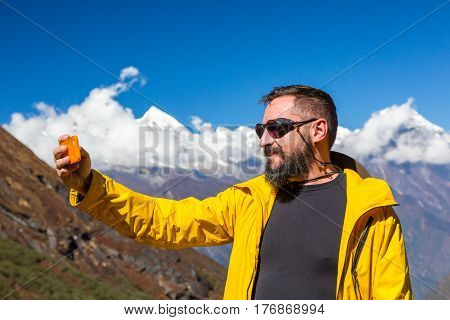 Smiling Bearded Person in bright sporty yellow Jacket taking Photo Self Portrait or Video with mobile Telephone in front of Mountain Panorama