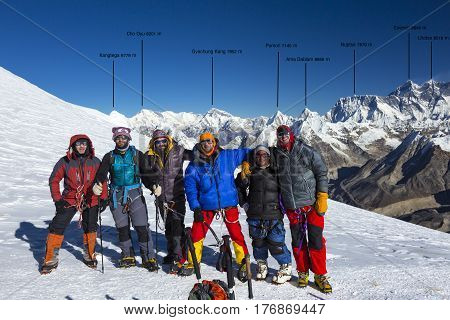 Group of Mountain Climbers in warm high altitude jackets and pants with gear and backpacks smiling and excited with Himalaya Summit Range with major peaks names and altitude.