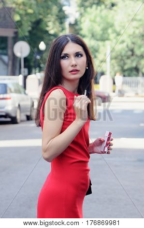 Girl with a cigarette in one arm and a cigarette pack in other turns around back