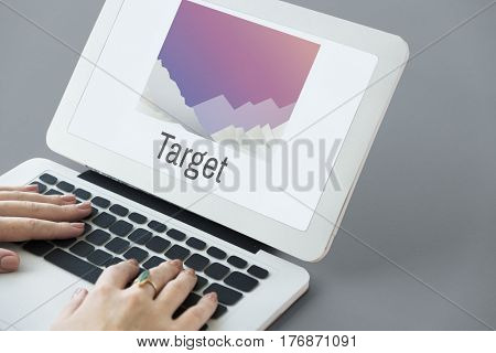 Hands using laptop with target on the screen