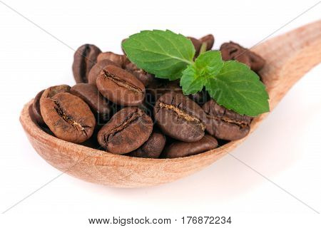 Coffee beans in a wooden spoon with leaf isolated on a white background.