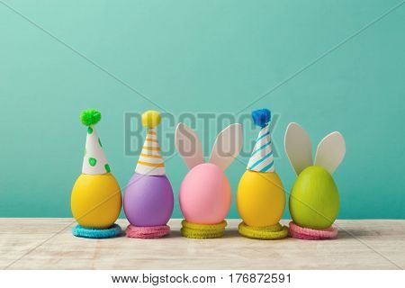 Easter holiday concept with cute handmade eggs bunny ears and party hats