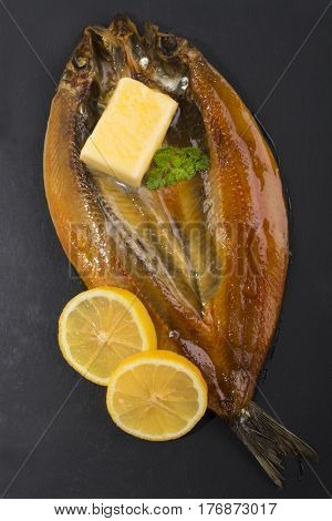 scottish smoked kipper with lemon butter and parsley on slate