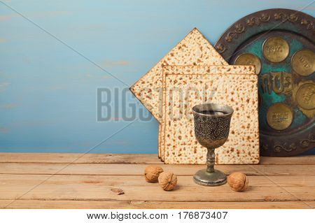 Jewish holiday Passover concept with vintage wine glass and seder plate on wooden table