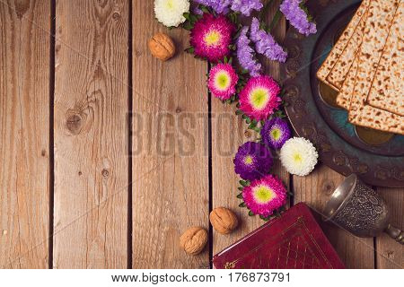 Jewish holiday Passover background with matza seder plate and spring flowers. View from above