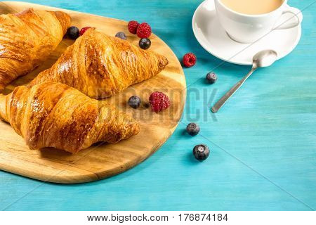 A photo of fresh crunchy croissants with blueberries and raspberries, with a cup of latte in the background, with a place for text