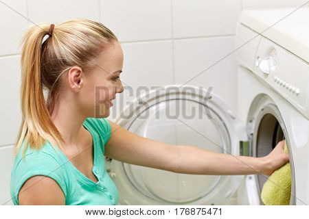 people, housework and housekeeping concept - happy woman putting laundry into washing machine at home bathroom
