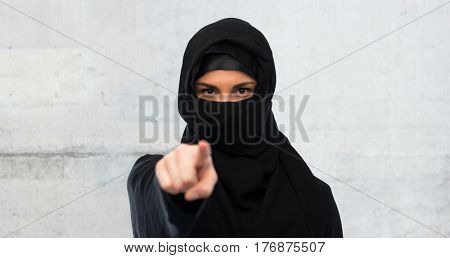 religious and people concept - muslim woman in hijab pointing finger to you over gray concrete wall background