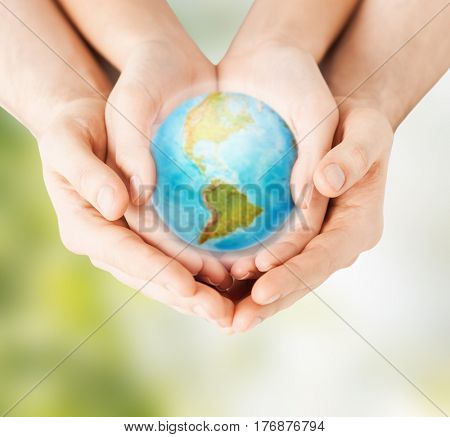 earth day, nature, conservation, environment and ecology concept - close up of woman and man hands holding planet over green natural background