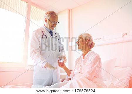 medicine, age, health care and people concept - doctor giving medication and water to senior woman at hospital ward