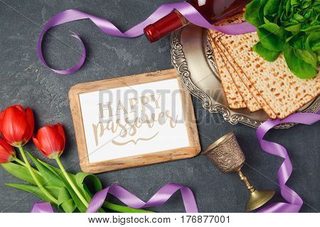Passover holiday concept matzoh photo frame and tulip flowers on dark background. Top view from above