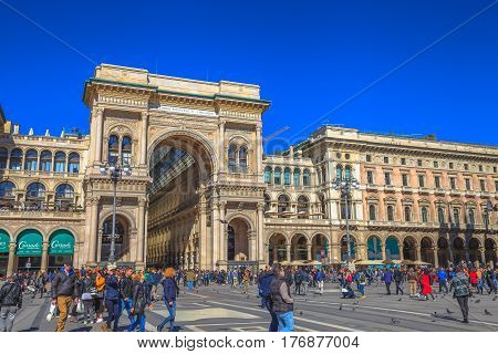 MILAN, ITALY- MARCH 7, 2017: Tourists in front of the Galleria Vittorio Emanuele II gallery doorway. In Piazza Duomo square.