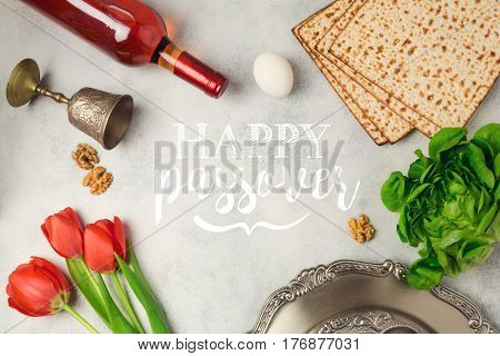 Jewish holiday Passover Pesah greeting card with seder plate matzoh and wine bottle.