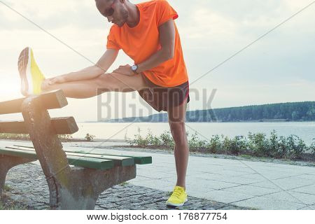Urban jogger stretching / exercising on the bench.