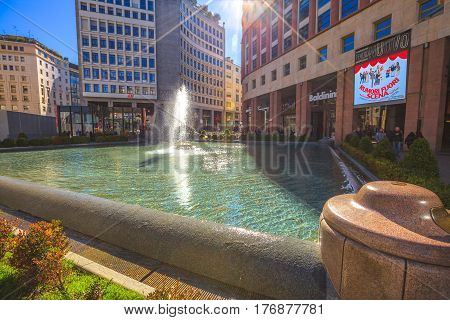 MILAN, ITALY- MARCH 7, 2017: the famous fashion square of Milano Piazza San Babila fountain at the end of Corso Vittorio Emanuele II from Piazza Duomo square of Milano.